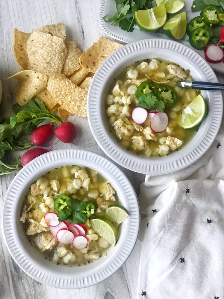 Two bowls of pozole verde with radishes to garnish. Tortilla chips on the side.