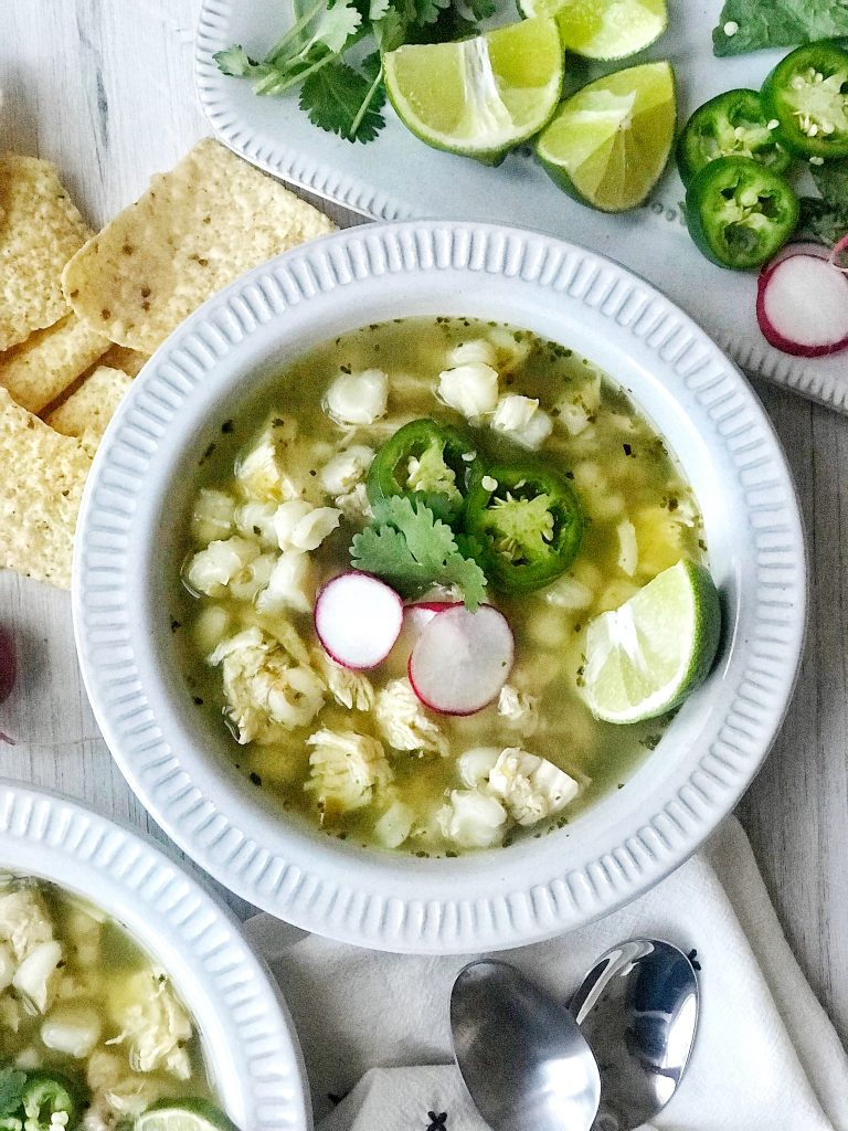 Bowl of green pozole with jalapeno, lime, and radish garnish. Tortilla chips to the side.