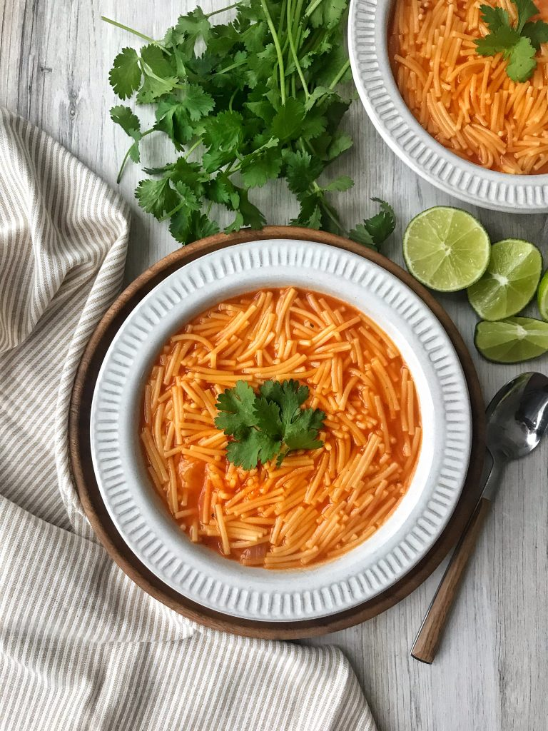 Mexican fideo in a bowl with cilantro and lime garnish