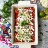 Casserole dish full of red enchiladas
