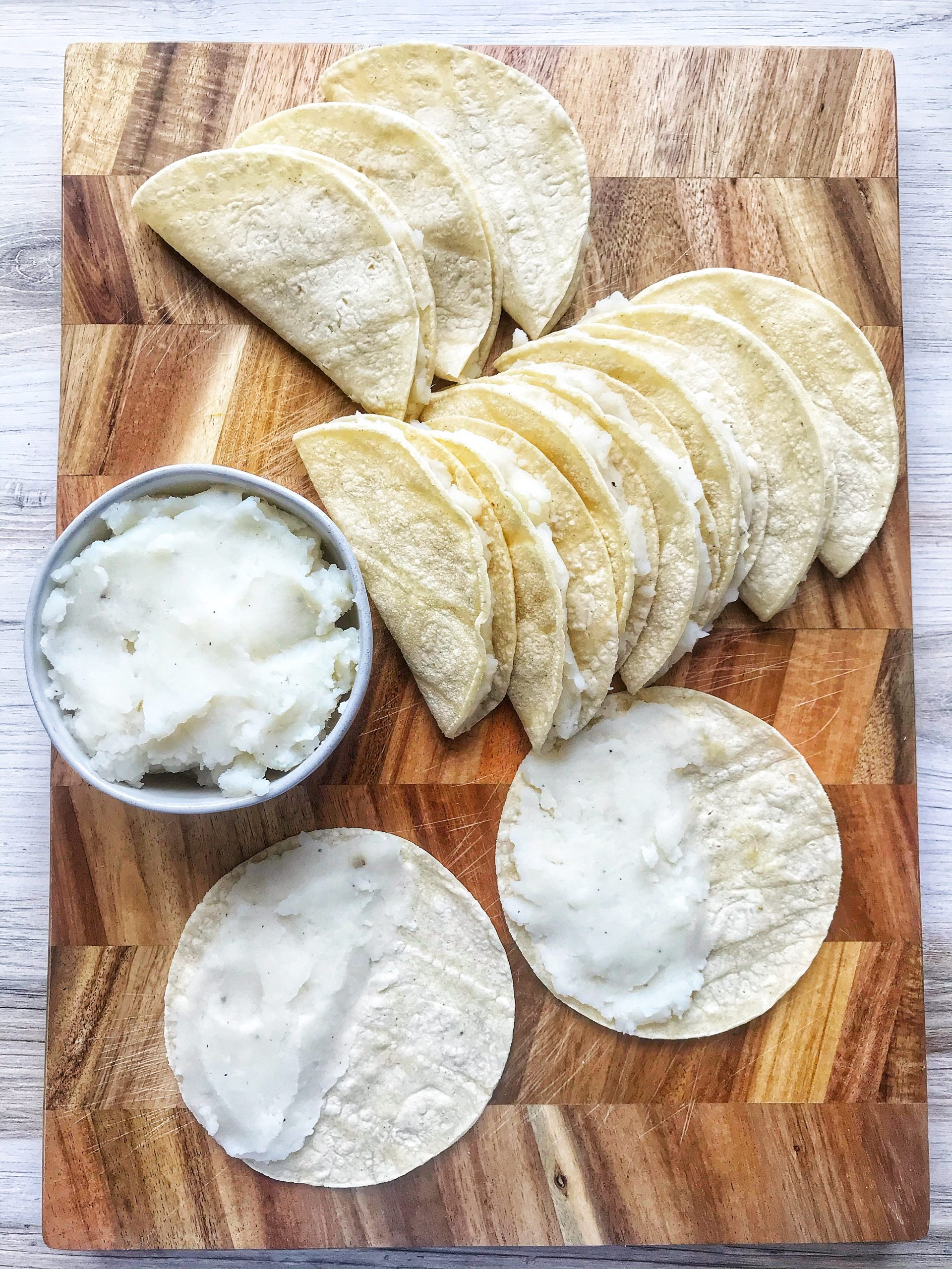 White corn tortillas filled with mashed potato. Open potato tacos and folded potato tacos.