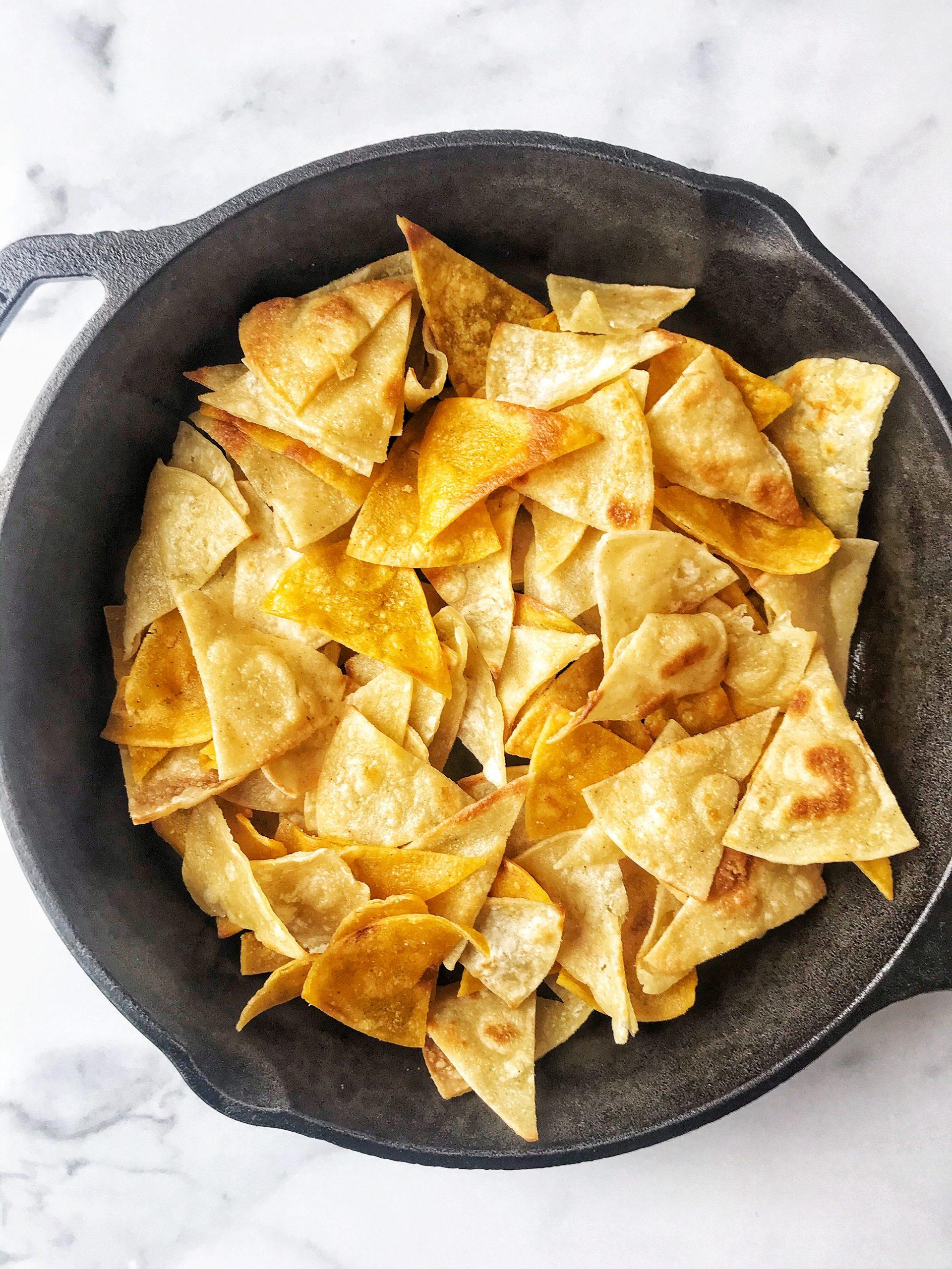Fried tortillas; tortilla chips in cast iron skillet