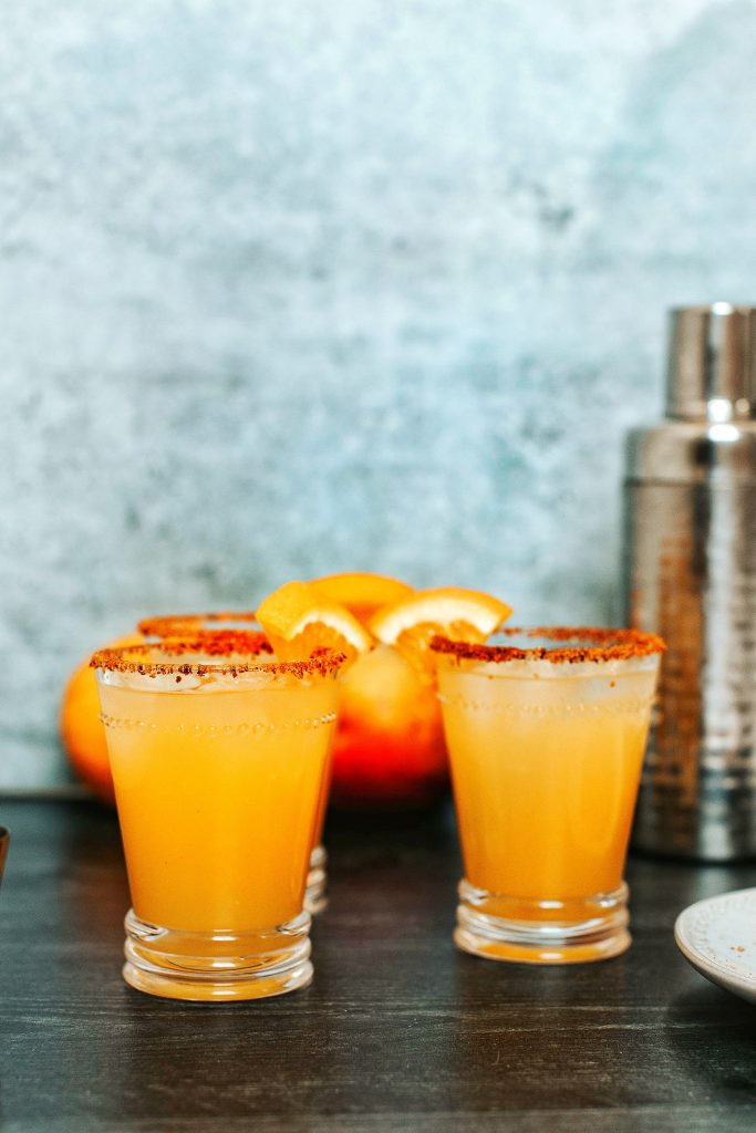 Three orange mango margaritas in small glass with Tajin rim. Shaker in background.
