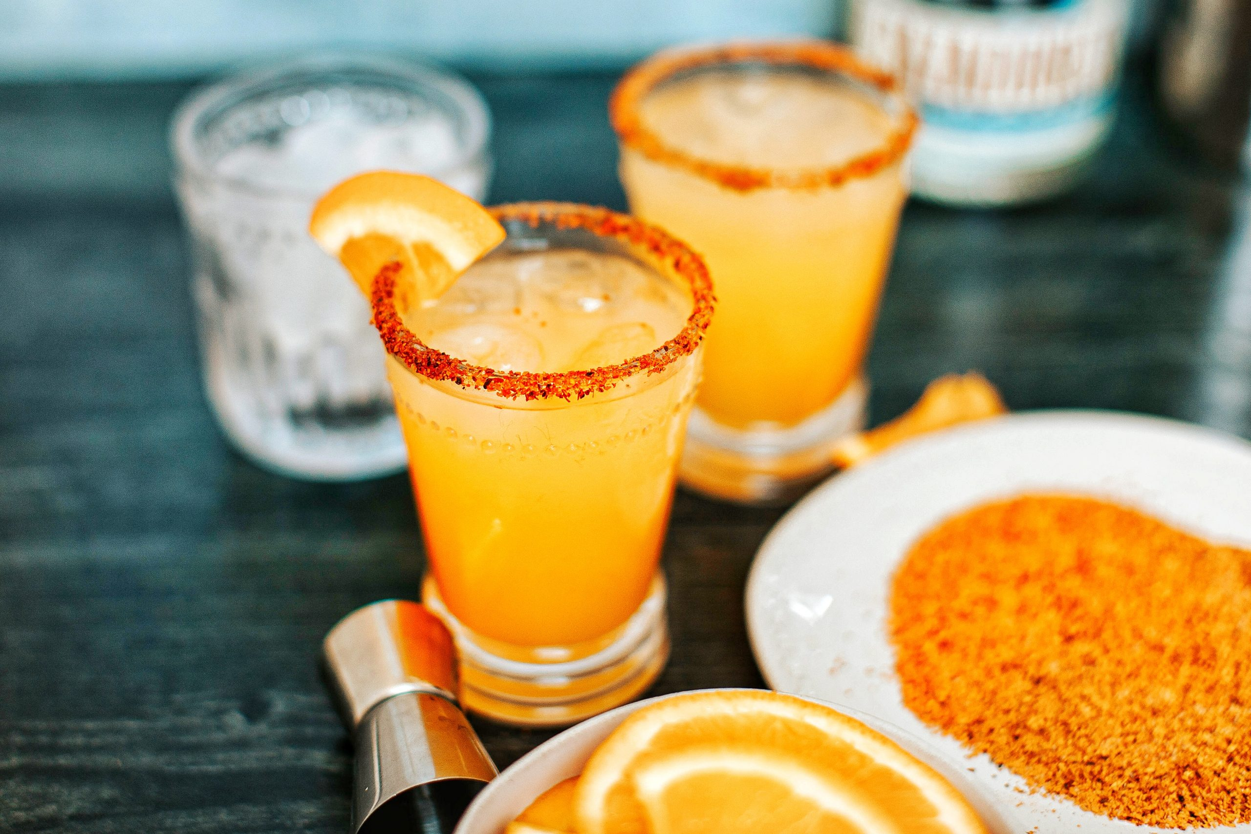 Orange mango margarita in glass with Tajin rim. Orange slices in bowl, Tajin on plate.