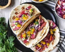 Ahi tuna tacos with slaw and mango on black plate