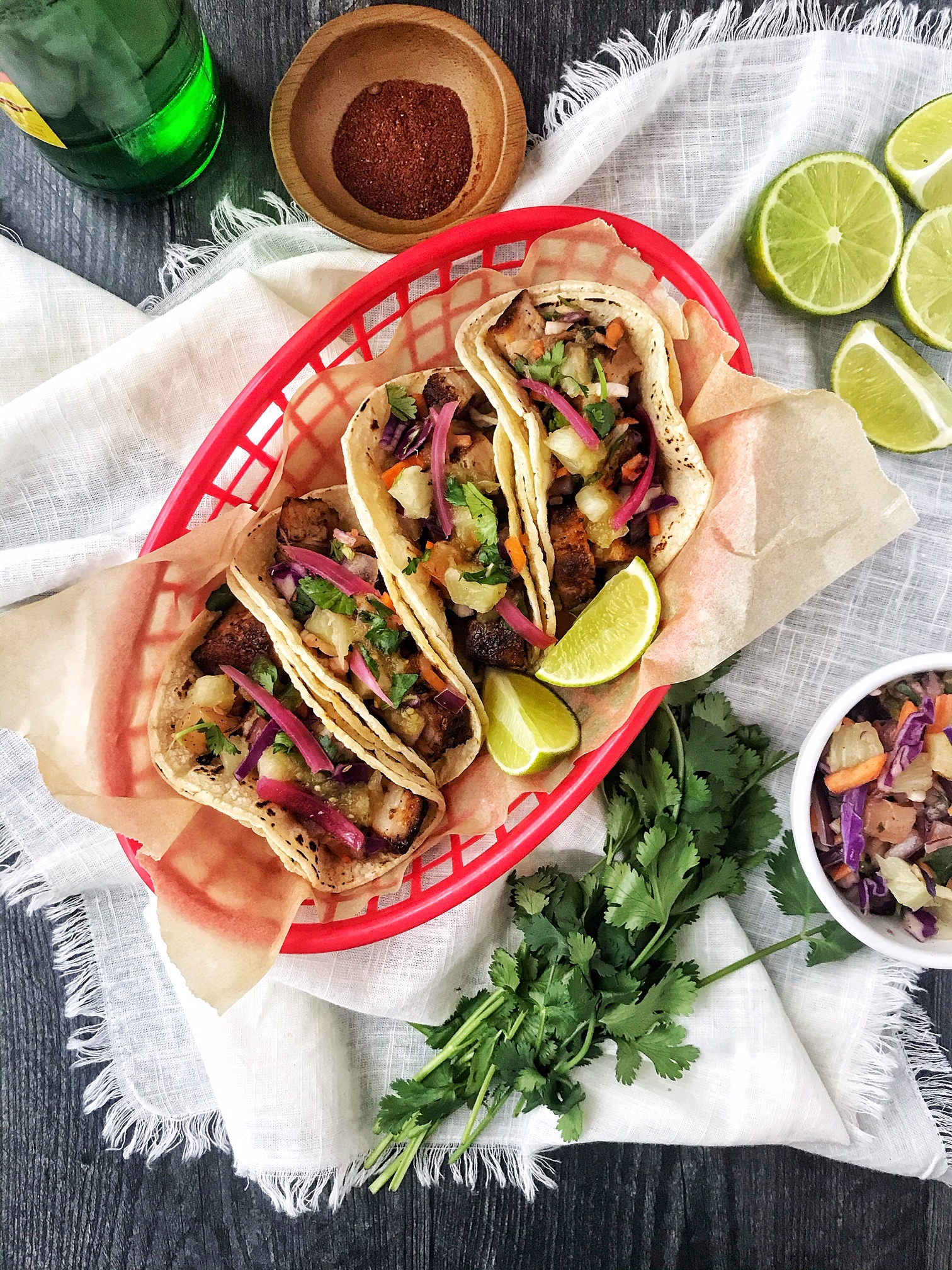 Pork belly tacos with pineapple slaw and red onion. Limes, chili powder, cilantro, and drink on the side.