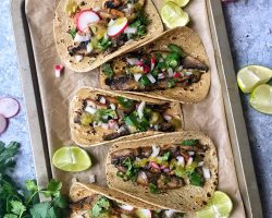 Mushroom Asada Tacos with onions, cilantro, salsa and radishes. Taco on baking sheet pan.