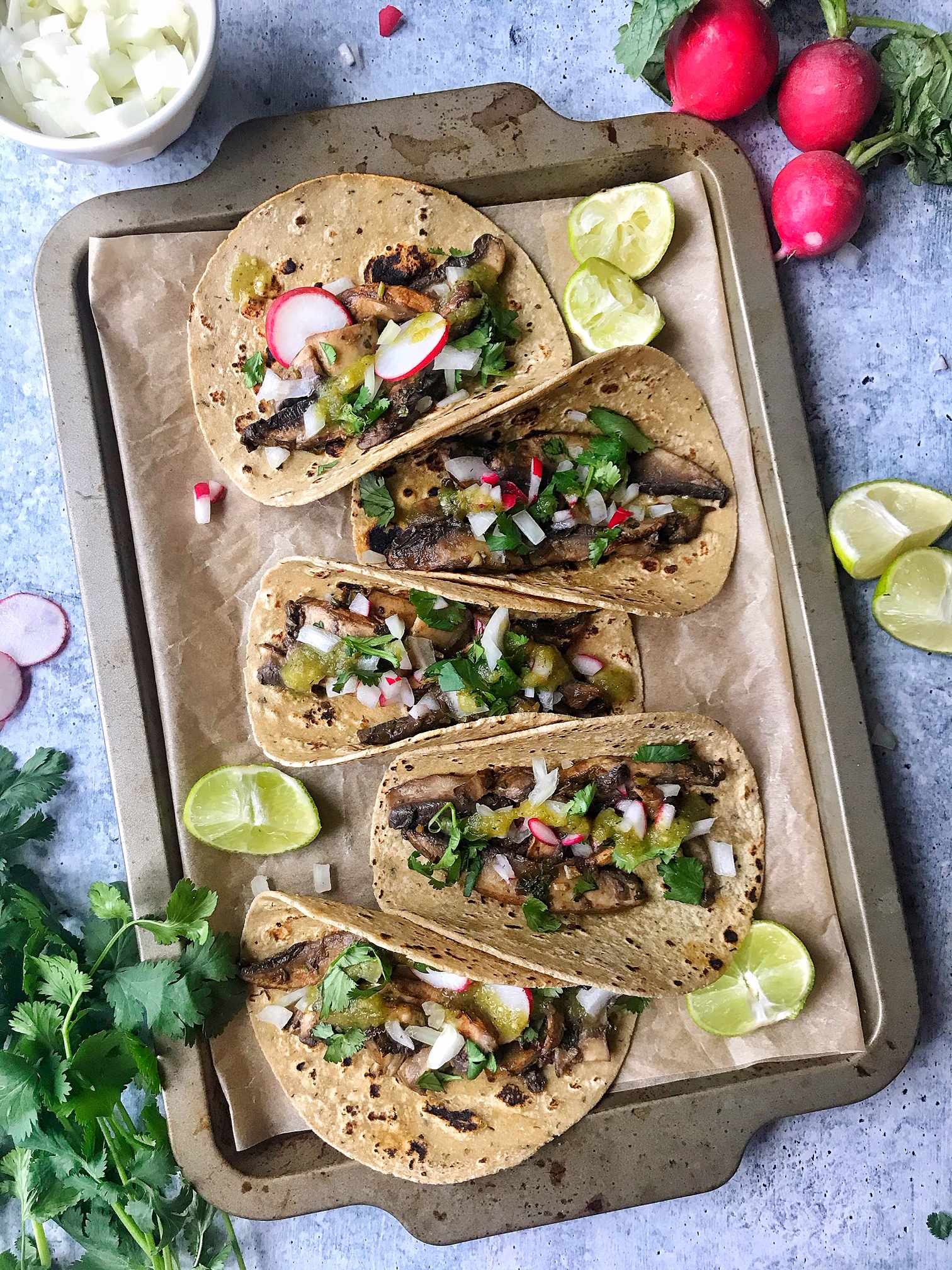 Mushroom Asada Tacos with onions, cilantro, salsa, and radishes. Tacos folded on a baking sheet.