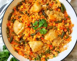 Large white pan with chicken and rice with vegetables