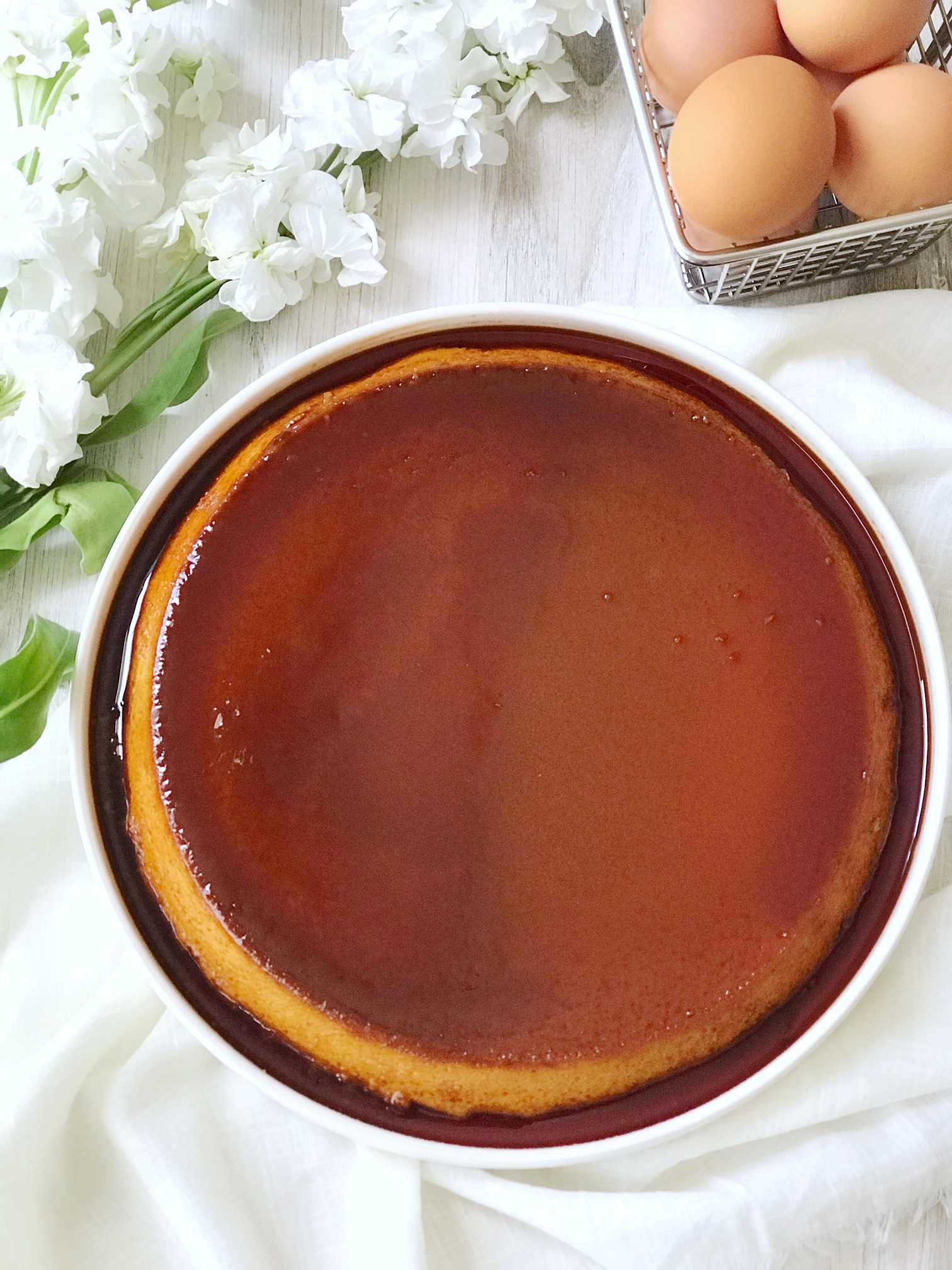 Mexican flan on large white plat with caramel sauce. Brown eggs and white flowers.
