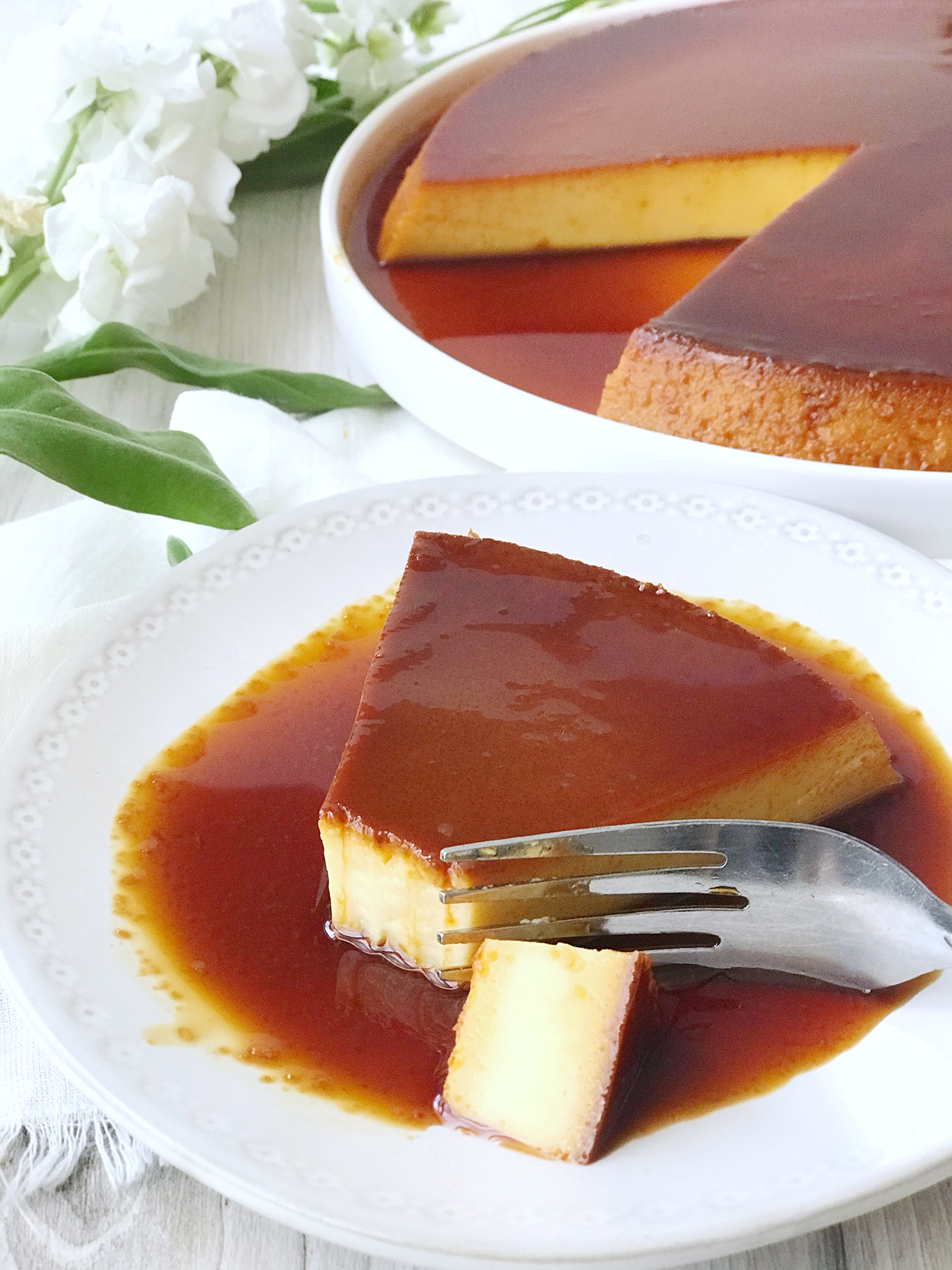 Mexican Flan on a large plate with caramel sauce and a slice missing. Slice of Mexican flan on small plate with piece cut off and a fork. White flowers in background.