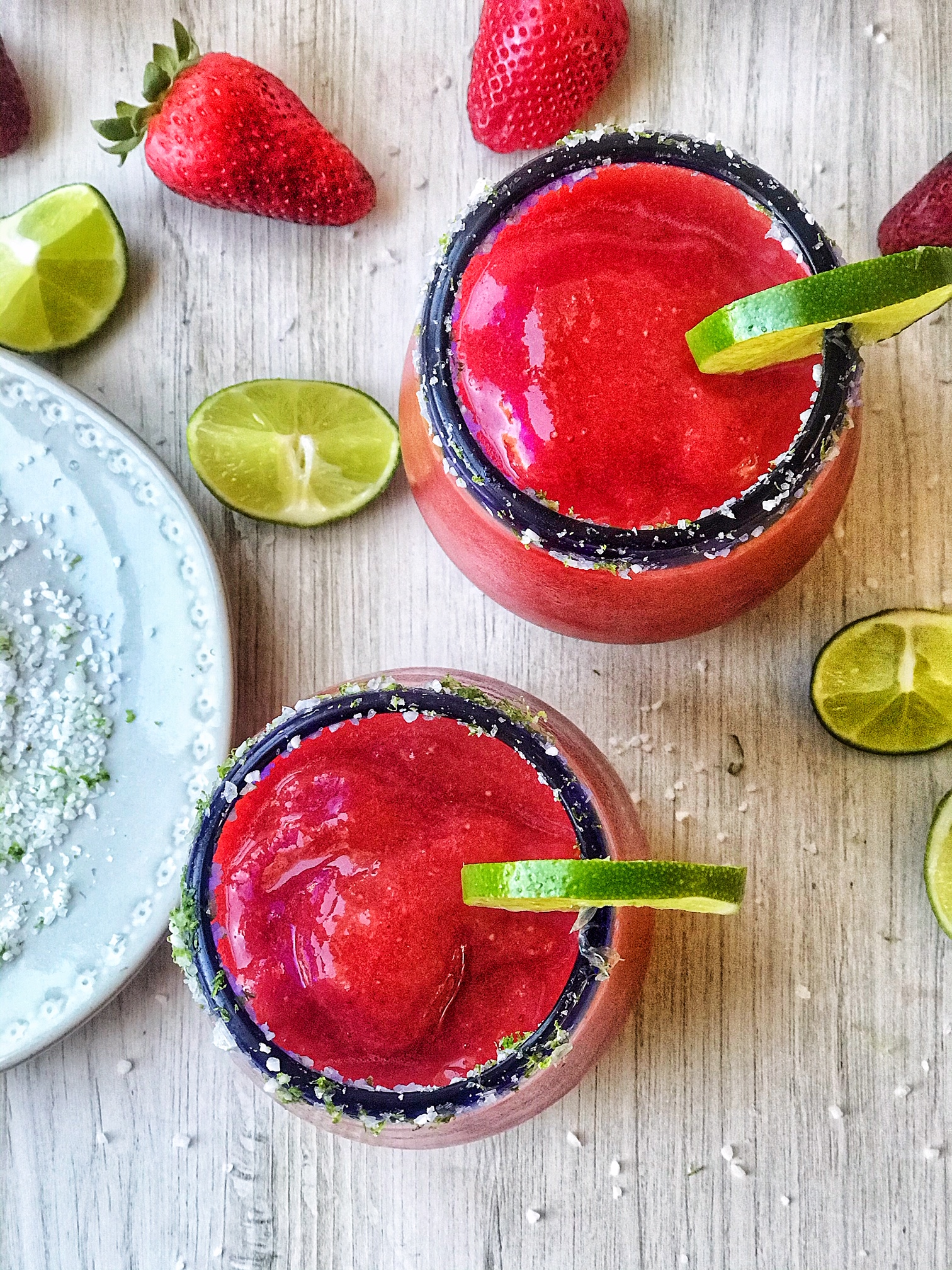 Two strawberry frozen margaritas with salt rim and limes. Limes and strawberries surround the margaritas. Small plate of salt and lemon zest.