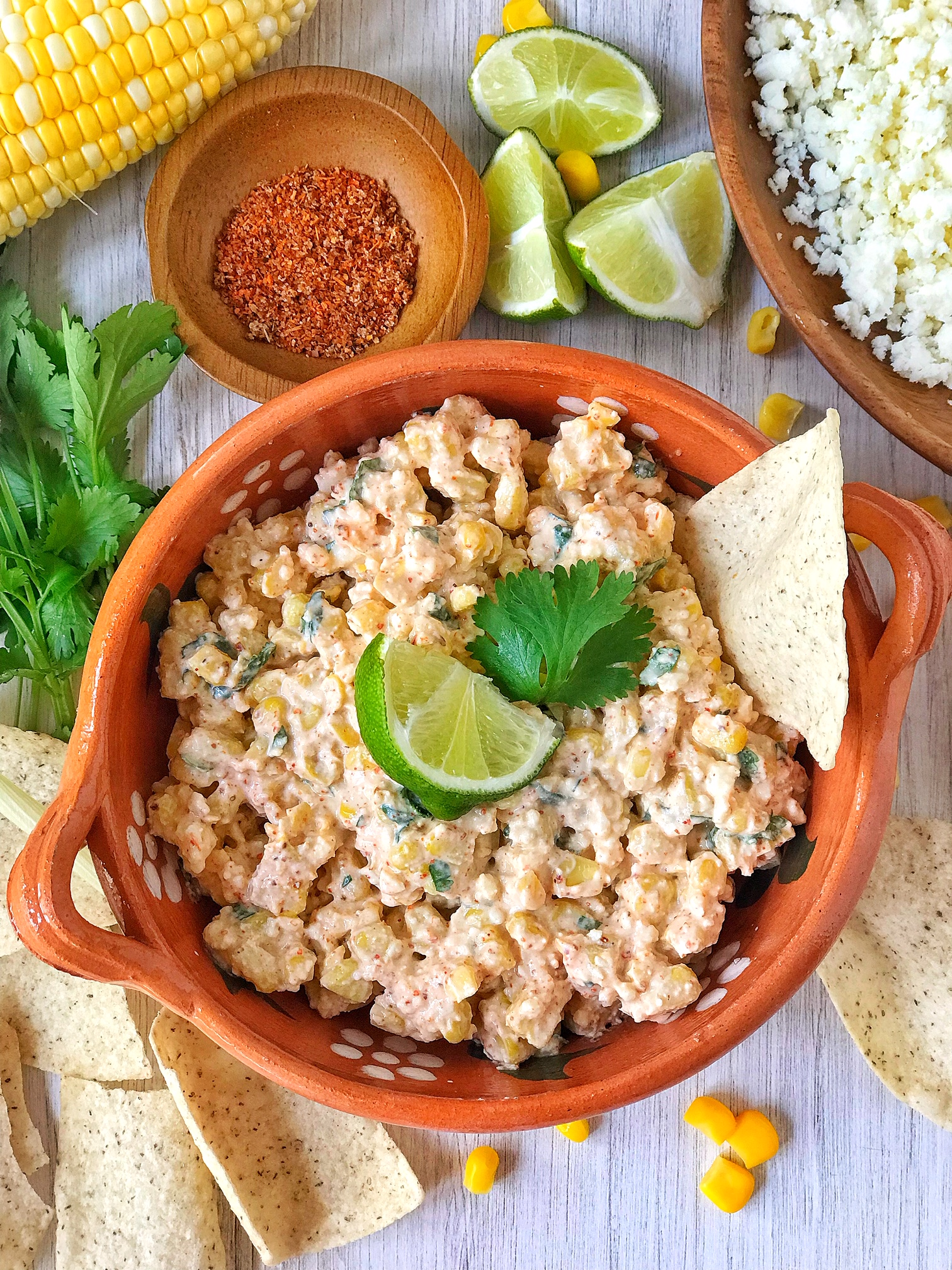 Bowl of Mexican street corn dip garnished with lime and cilantro, tortilla chip in dip. Corn, limes, crumbled cheese, and tortilla chips in picture.
