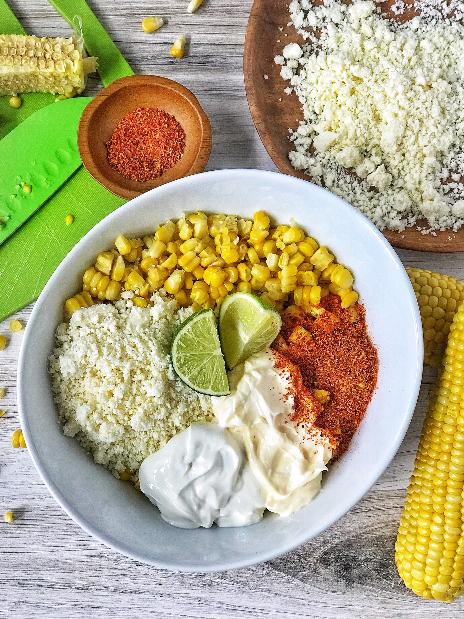 White bowl with Mexican street corn dip ingredients. White bowl with corn, crumbled cheese, mayo, sour cream, Tajin, and lime. Corn and crumbled cheese in picture.