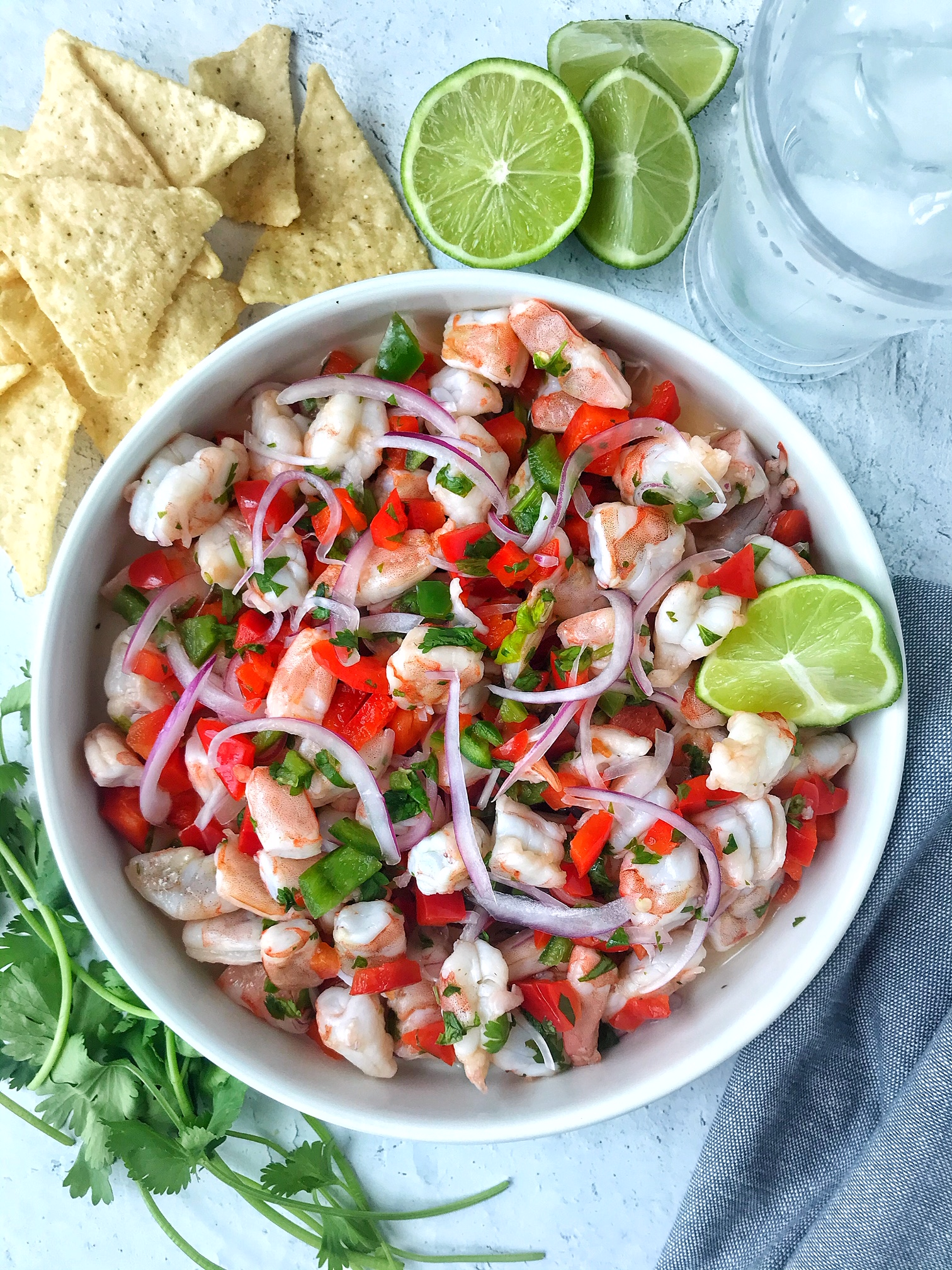 White bowl with shrimp ceviche with red peppers, cilantro, red onions, and lime. Tortilla chips, lime, and cilantro garnish