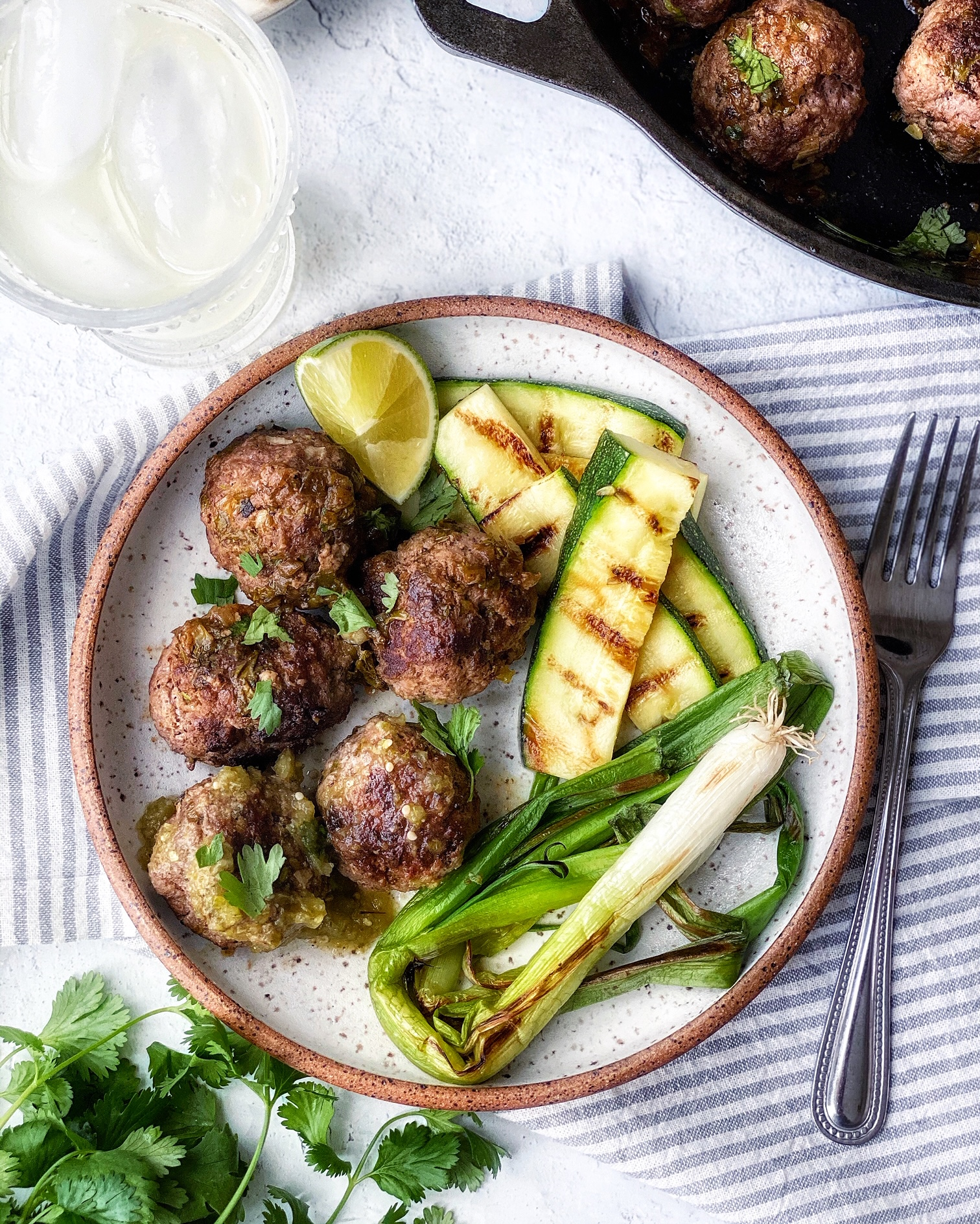 Carne asada meatballs, grilled zucchini, grilled green onions on a plate