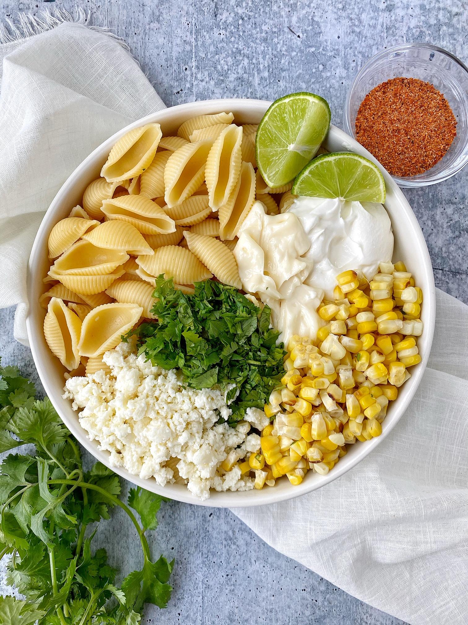 Pasta, sour cream, crumbled cheese, cilantro, and corn in a white bowl. Lime garnish, cilantro garnish, chili powder on the side.