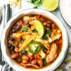 Bowl of southwest chicken enchilada soup with tortilla strips, jalapeno, and lime