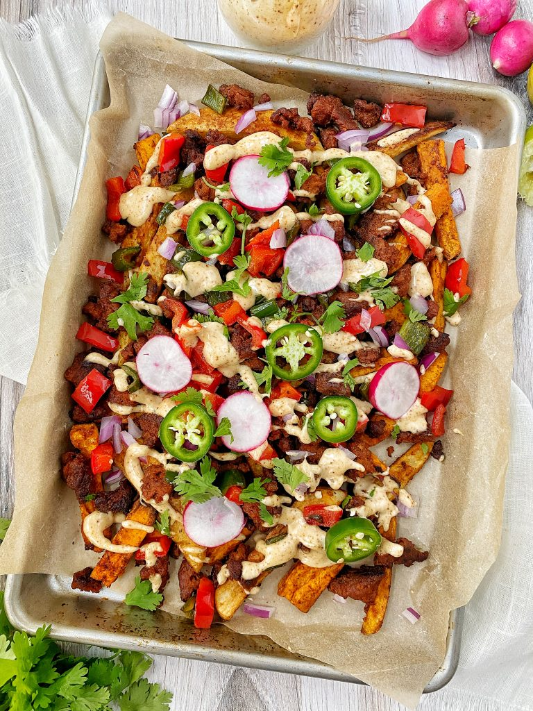 Pan of loaded chorizo fries with red peppers, radishes, jalapenos, and onion
