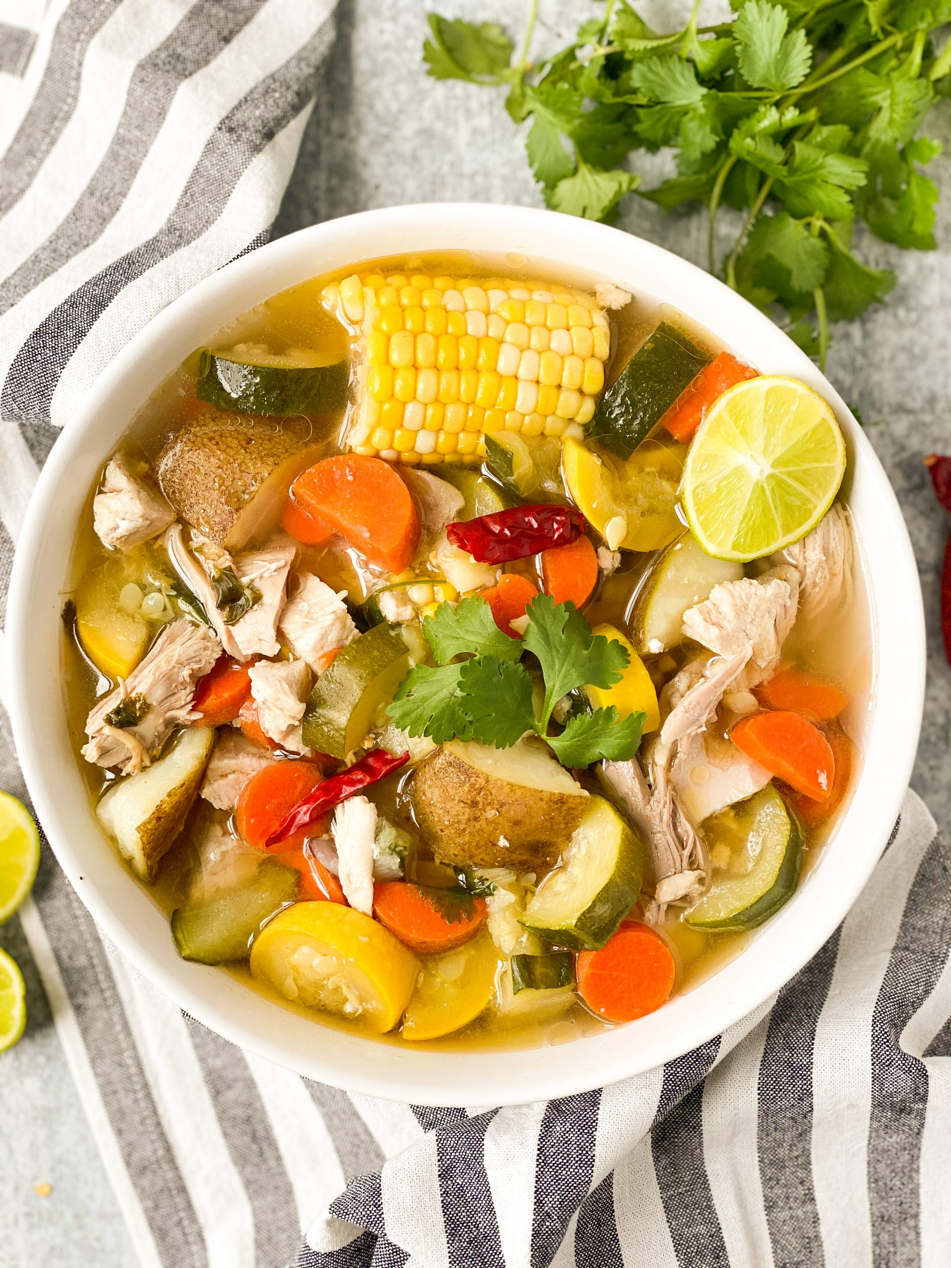White bowl with caldo de pollo, mexican chicken soup. Includes potatoes, zucchini, carrots, and corn. Striped towel under bowl.
