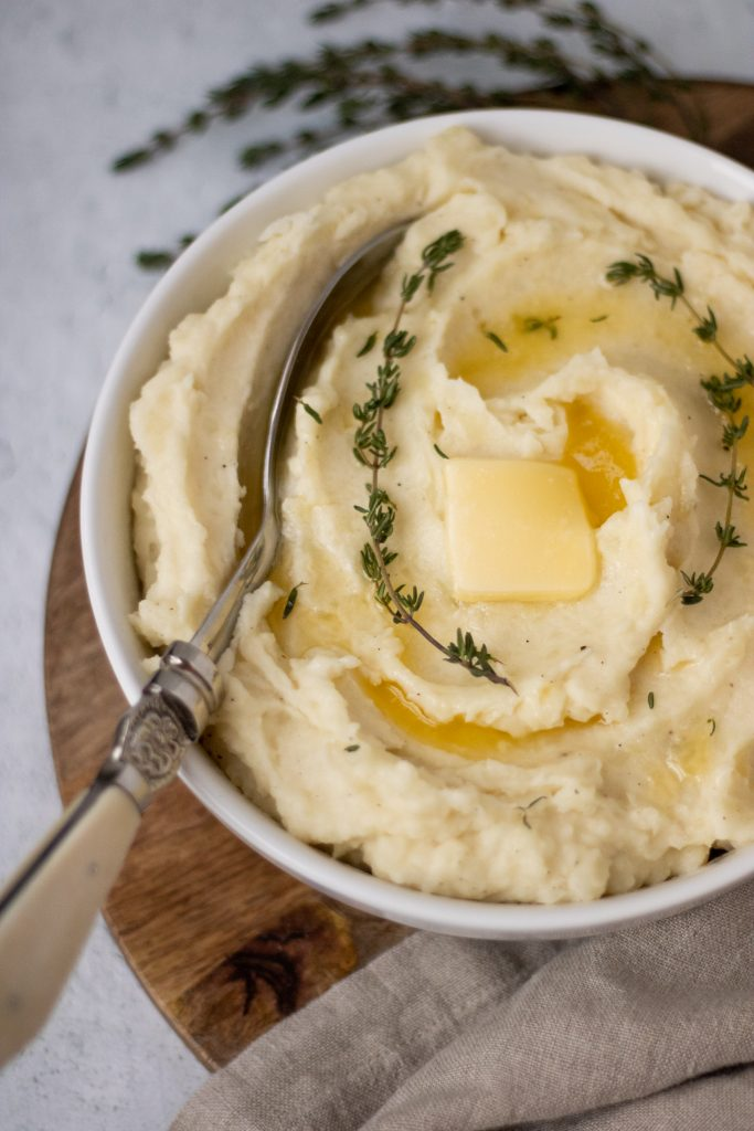 white bowl of mashed potatoes with butter and thyme sprigs. Serving spoon in mashed potatoes.