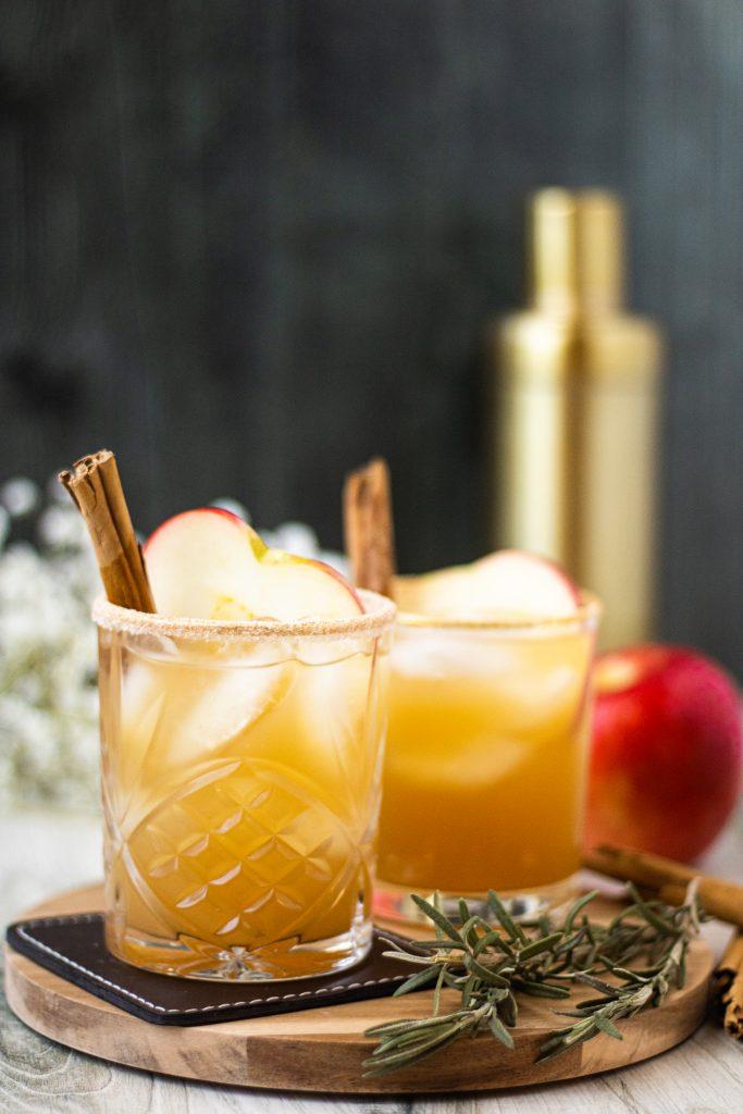 2 glasses of apple cider margaritas. Apple slice and cinnamon stick garnish