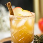 Apple cider margarita in a glass with a slice of apple and a cinnamon stick garnish.