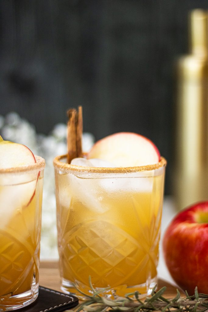 Apple  cider margarita with apple slice and cinnamon stick garnish. Apple on side