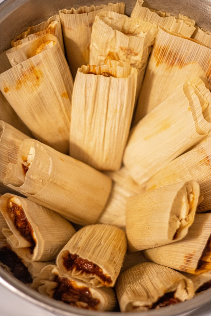 Pot full of tamales wrapped in corn husks