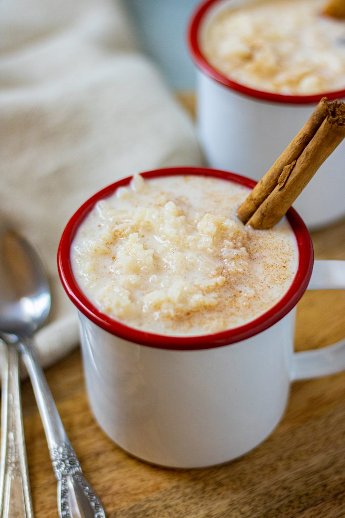 White mugs with red rims filled with arroz con leche. Garnished with a cinnamon stick.