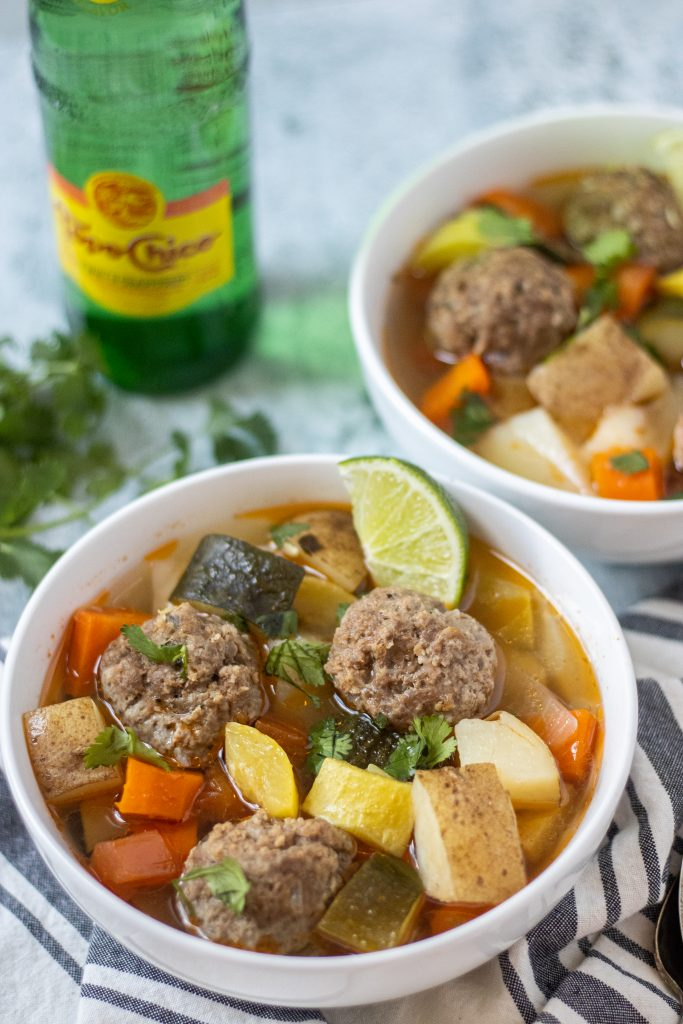 White bowl filled with albondigas, or meatballs, vegetables, and lime wedge garnish.