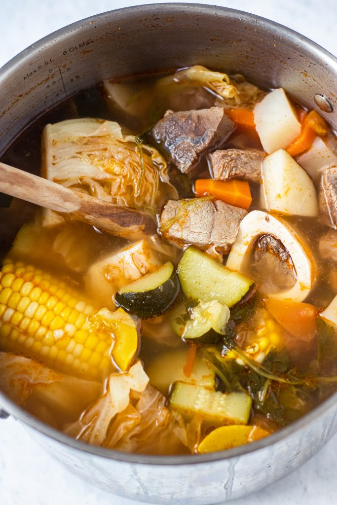 Large pot with caldo de res with corn, zucchini, carrots, cabbage, and beef.