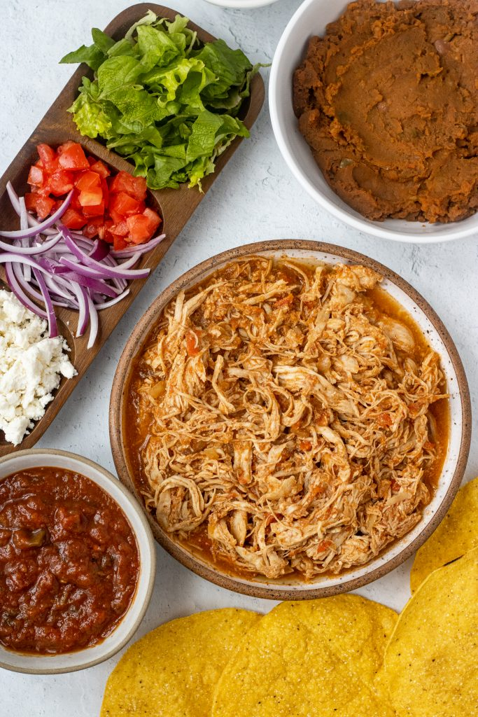 Ingredients for chicken tinga tostadas. Chicken tinga, salsa, cheese, onion, tomatoes, lettuce, refried beans, tostada shells