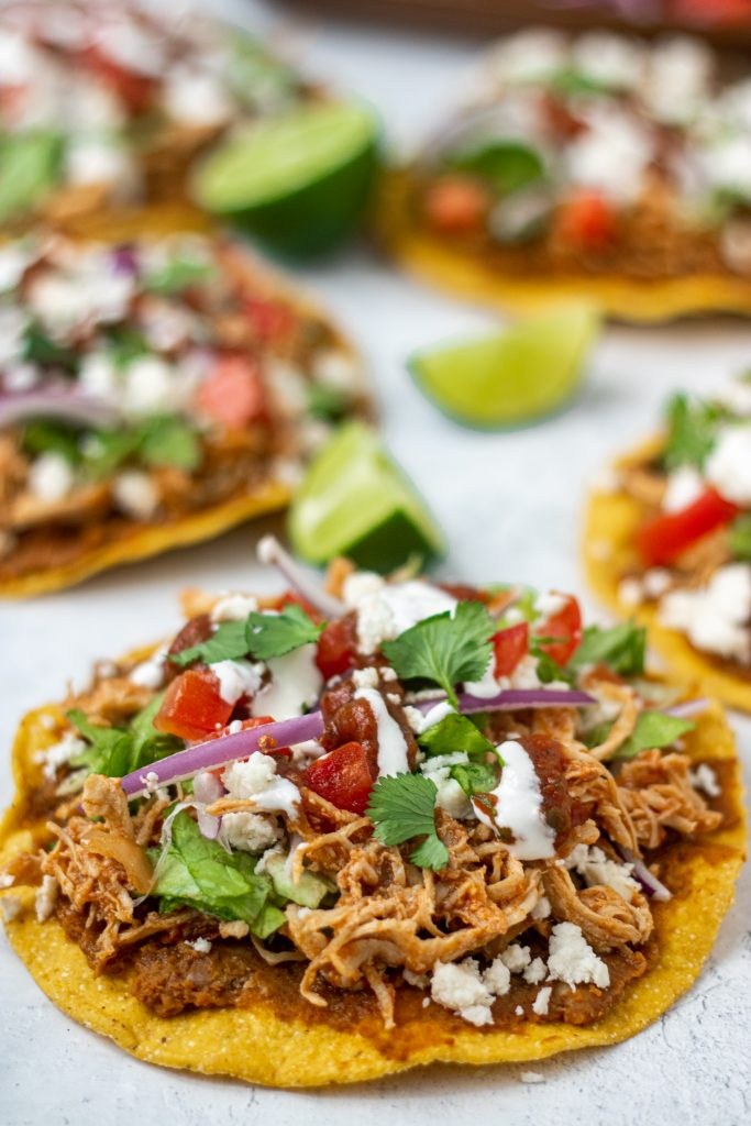 Close up of chicken tinga tostadas with tomato, onion, lettuce, sour cream, cheese.