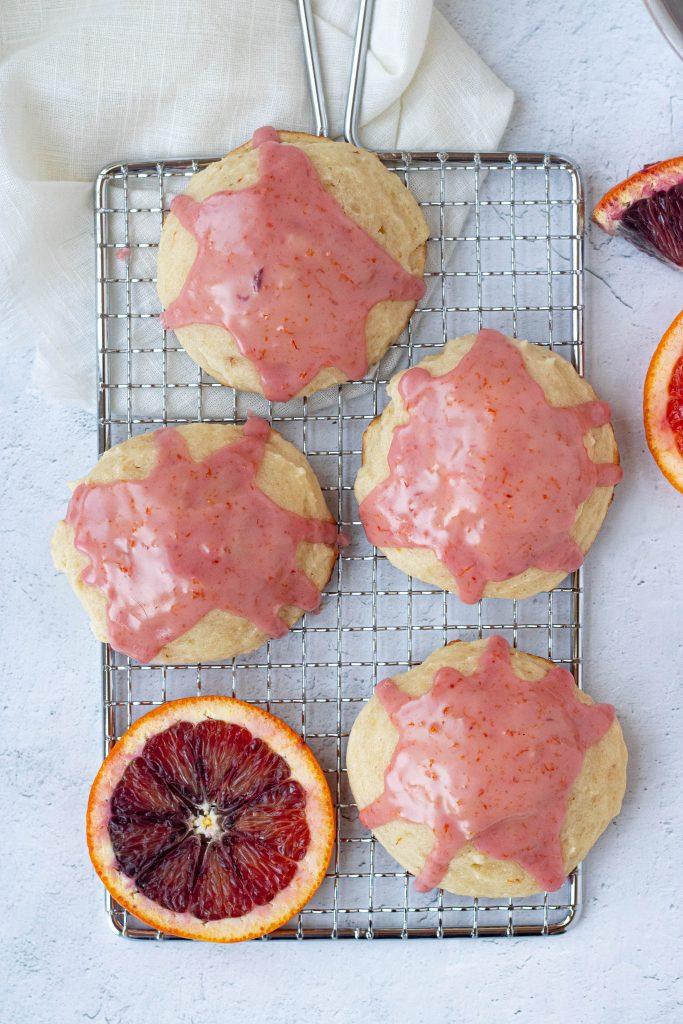 Four blood orange ricotta cookies with pink glaze. Slice of blood orange.