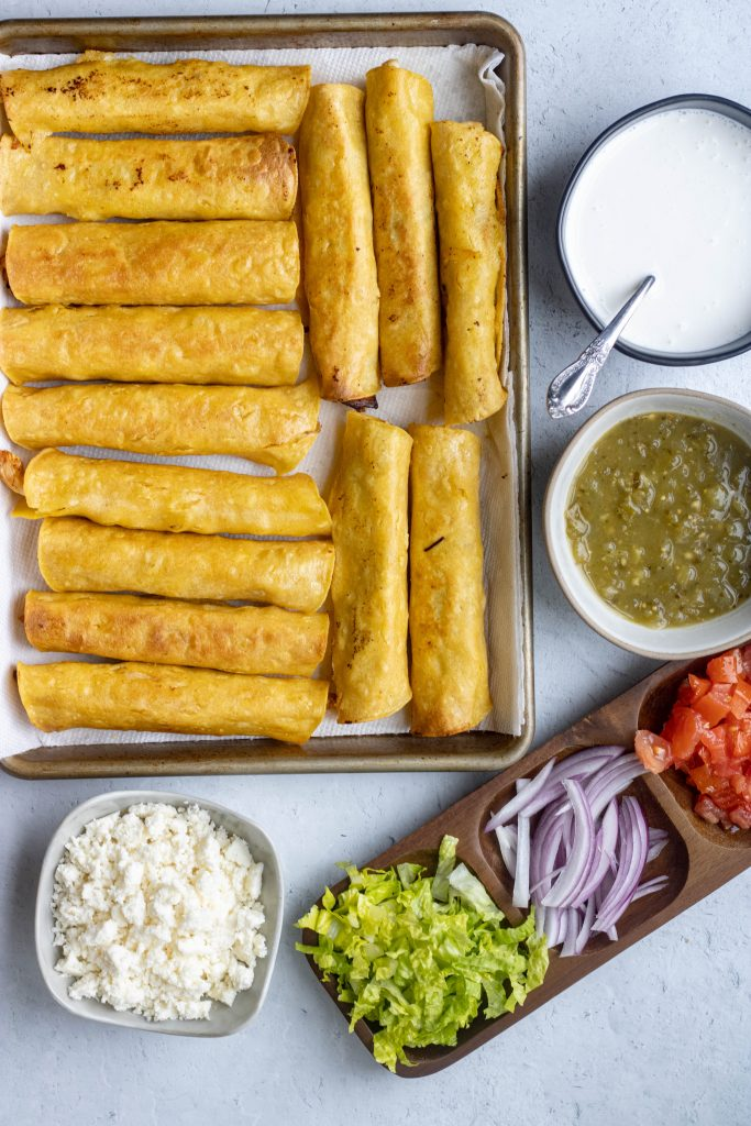 Tray of flautas. Sides of toppings including sour cream, queso fresco, onions, tomatoes, shredded lettuce, and salsa verde.