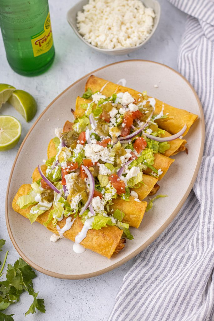 Plate of chicken flautas topped with shredded lettuce, tomatoes, onions, sour cream, queso fresco, and salsa verde.