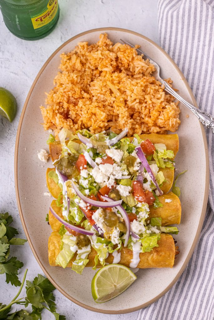 Platter of flautas with side of rice. Flautas topped with lettuce, onion, tomato, queso fresco, sour cream, and salsa.