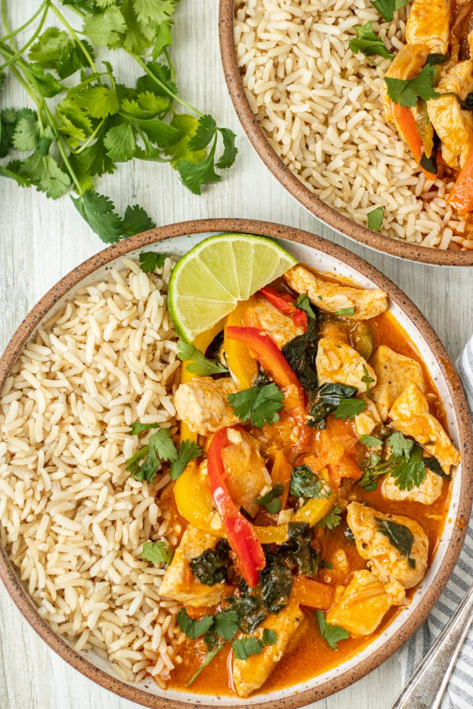 Bowl with Thai Lemongrass Curry with brown rice and lime garnish. Cilantro garnish