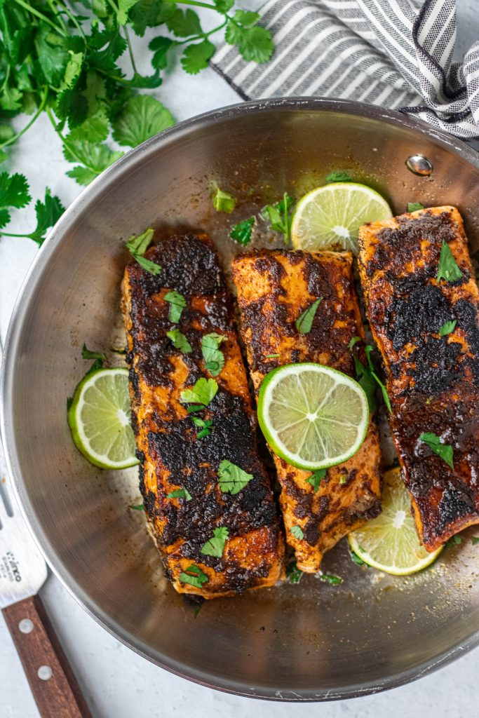 Chili Lime Salmon in stainless steel pan. Lime and cilantro garnish
