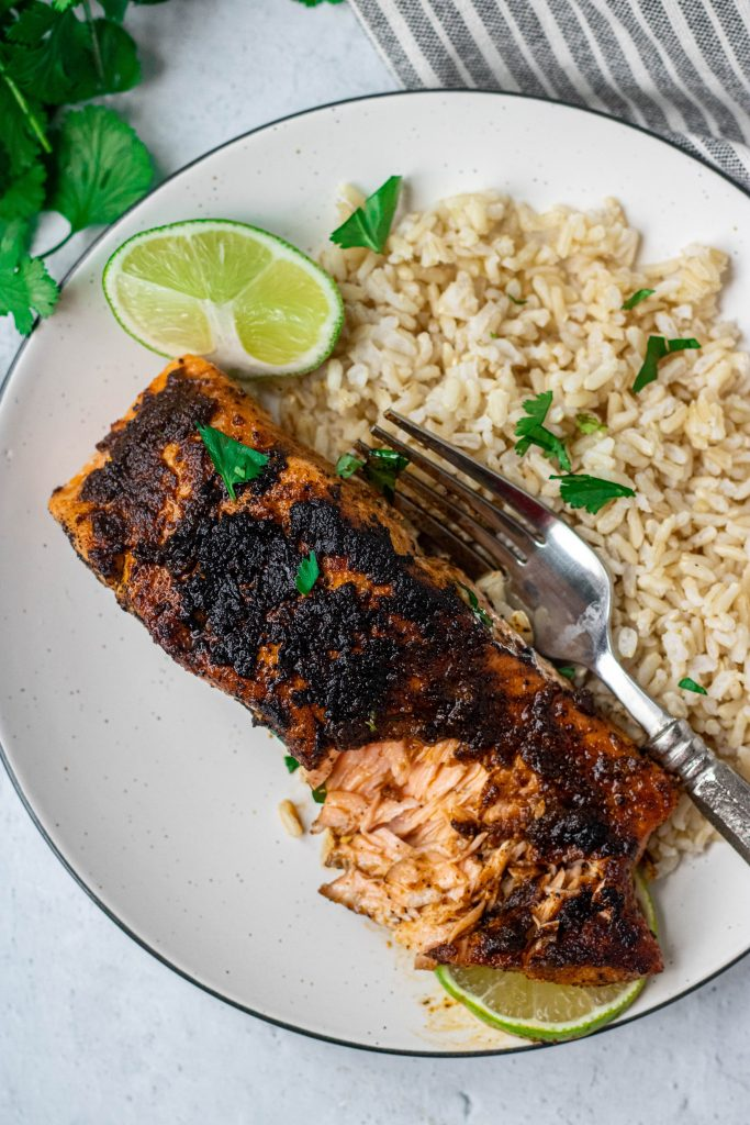 Chili Lime Salmon on white plate with side of rice and fork. Lime and Cilantro garnish