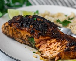 Chili lime salmon on a white plate with rice