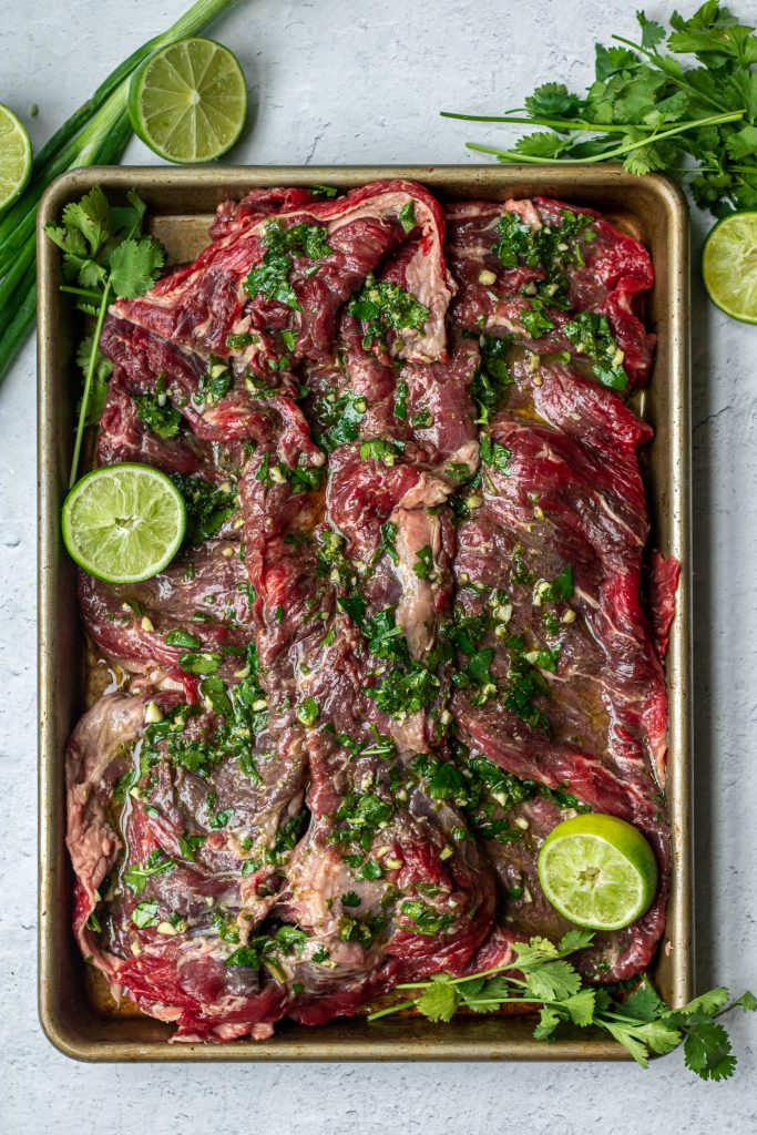 Arracher, skirt steak, with marinade. Cilantro and lime garnish all on small sheet pan.
