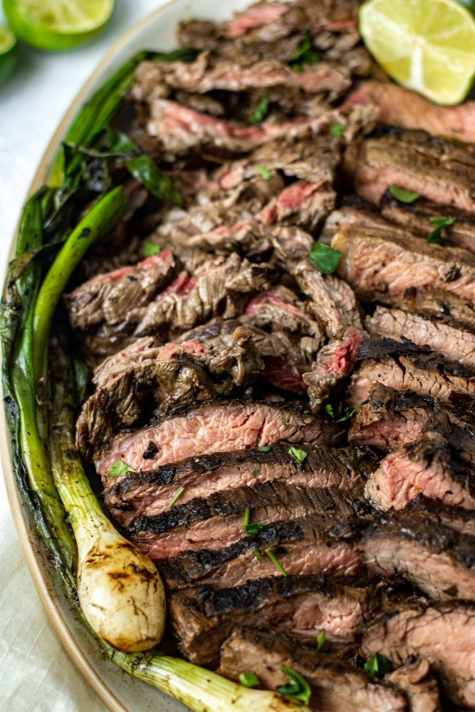 Close up of platter with sliced Mexican Carne Asada. Green onion garnish