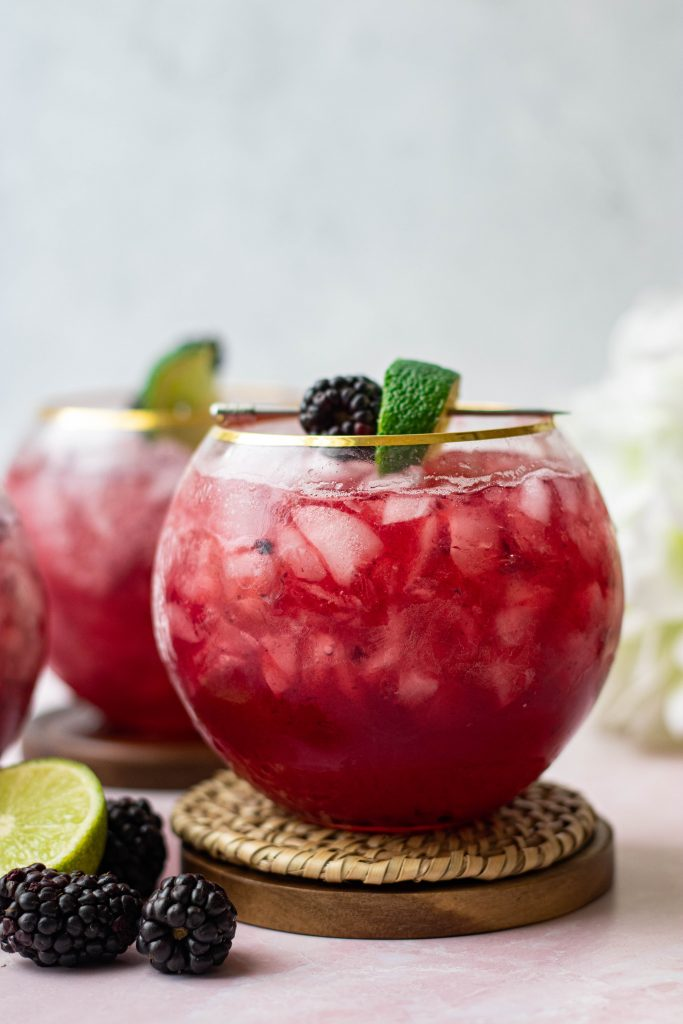 Blackberry Bourbon smash on coaster with lime and blackberry garnish