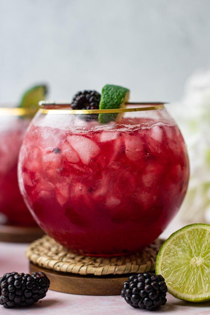Close up of Blackberry Bourbon Smash. Blackberries and lime garnish