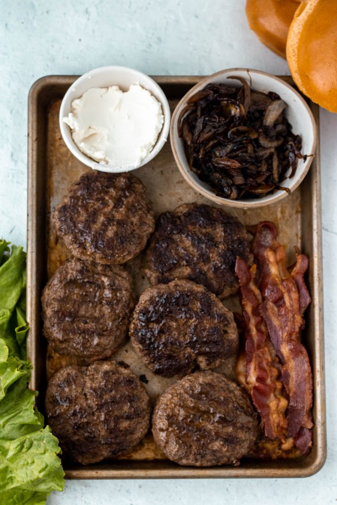 Ingredients for burgers including goat cheese, caramelized onions, burger patties, bacon, buns, and lettuce