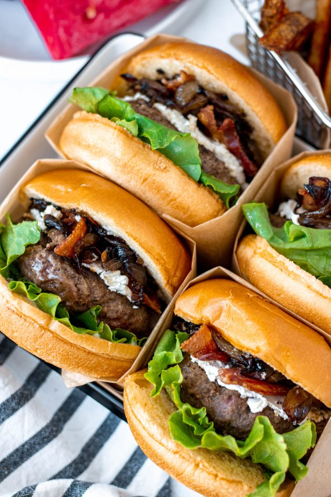 Close up of four Bacon Goat Cheese Burgers with Balsamic Caramelized Onions. Burgers wrapped in brown paper.