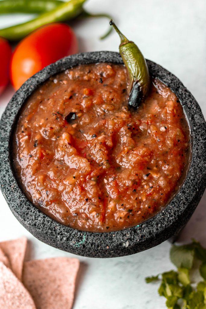 Salsa Roja in stone molcajete. Serrano pepper garnish, tomato prop