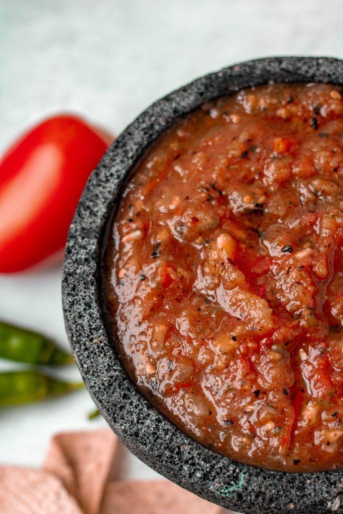 Close up of salsa roja in stone molcajete. Tomato and serrano pepper props